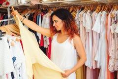 Młoda ładna kobieta próbuje na nowej sukni w sklepie odzieżowym tła karciana powitania strony zakupy szablonu czas cechy ogólnej  Obraz Stock