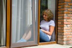 Młoda ładna kobieta siedzi na windowsill i czyta książkę fotografia royalty free