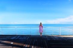 Młoda ładna kobieta stoi samotnie na molu blisko morza fotografia royalty free