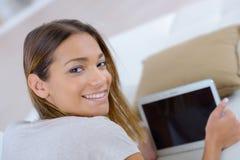 Młoda ładna kobieta używa laptop na kanapie obraz royalty free
