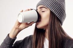 Młoda ładna kobieta w popielatym kapeluszowym napoju kawa od papierowej filiżanki zamknięte oczy Takeaway pakunek dla układu Zdjęcia Stock