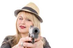 Młoda ładna kobieta wskazuje pistolet przy kamerą z jeden ręką, zdjęcie royalty free