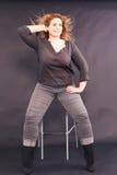 Młoda ładna kobieta z z nadwagą obsiadaniem na prętowej stolec obrazy stock