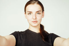 Młoda ładna nastoletnia dziewczyna robi selfie odizolowywającemu up na białym tła zakończeniu Fotografia Stock