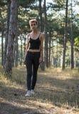Młoda Ładna Punkowa dziewczyna w Czarnym płótnie z Różowym włosy w Sosnowym lesie przy zmierzchu czasem obraz stock