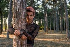 Młoda Ładna Punkowa dziewczyna w kołnierzu i Czarnym płótnie z Różowymi włosów uściśnięciami Drzewnymi w Sosnowym lesie przy zmie obraz royalty free