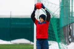 Młoda śliczna aktywna chłopiec w czerwonym i błękitnym sportswear rzucie futbolowa piłka za na od zimy pola z śniegiem na tle zdjęcia stock