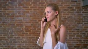 Młoda śliczna caucasian blondynki kobieta opowiada na telefonie komórkowym, gestykuluje, ściana z cegieł w tle