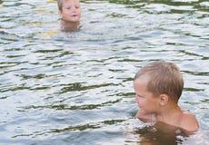 Młoda śliczna chłopiec i jego młodszy brat bawić się w wodzie w pięknym jeziorze na pogodnym letnim dniu lub rzece zdjęcia royalty free