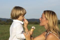 Młoda śliczna chłopiec z jego matką, je smakowitego lody Zdjęcie Stock