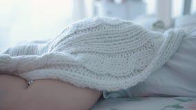 Młoda śliczna dziewczyna śpi w ranku w łóżku, jej noga jest ledwo widoczna spod koc, w górę, zwolnione tempo zdjęcie wideo
