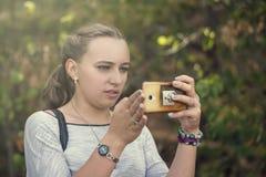 Młoda śliczna dziewczyna koncentruje na telefonie komórkowym podczas gdy na na obraz stock