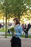 Młoda śliczna dziewczyna z kwiatami otrzymywał wiadomość lub wzywał ona zdjęcie stock