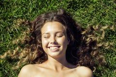 Młoda śliczna lato dziewczyna na trawie na zewnątrz relaksować zdjęcia royalty free