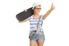 Młoda żeńska łyżwiarka daje kciukowi up Zdjęcia Royalty Free