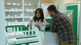 Młoda żeńska farmaceuta hrlping męskiego klienta kupować pastylkę przy apteką Zdjęcie Stock