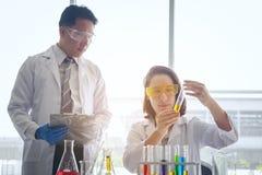 Młoda żeńska naukowiec pozycja z techer w lab pracownika robić zdjęcie stock