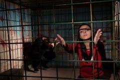 Młoda żeńska ofiara więziąca w metal klatki dojechaniu wręcza th Fotografia Royalty Free