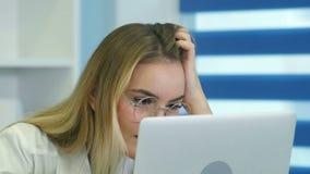 Młoda żeńska pielęgniarka w szkłach używać laptop przy biurkiem w medycznym biurze zdjęcie wideo