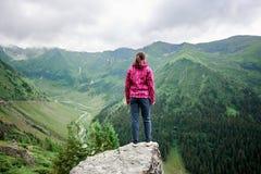 Młoda żeńska turystyczna pozycja na rockowej krawędzi wśród wspaniałych zielonych gór z trawiastymi skłonami zdjęcia stock