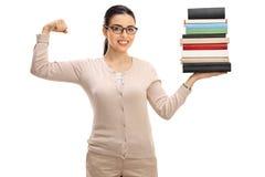 Młoda żeńskiego nauczyciela mienia sterta książki i napinać bicepsy fotografia royalty free