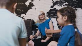 Młoda żeńskiego nauczyciela nauczania postać daje matematyki lekci chłopiec i dziewczyny w dziecinu Nauczyciel uczący zdjęcie wideo