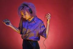 Młoda afro amerykańska kobieta słucha muzyka od jej retro spaceru Obrazy Stock