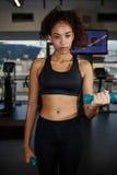 Młoda afro kobieta ćwiczy z bezpłatnymi ciężarami przy sprawności fizycznej centrum Zdjęcia Stock