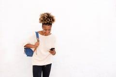 Młoda afro kobieta patrzeje telefon komórkowego na białym tle Obraz Stock