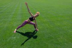 Młoda afroamerykańska dziewczyna w czarnej koszulce, menchii spodniach i sneakers robi sportom, ćwiczy na zielonej trawie i podno Fotografia Royalty Free
