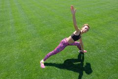 Młoda afroamerykańska dziewczyna w czarnej koszulce, menchii spodniach i sneakers robi sportom, ćwiczy na zielonej trawie i podno Obraz Royalty Free