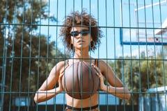 młoda afroamerykańska kobieta trzyma koszykówkę balowa w jej rękach przed jej klatką piersiową w sportach stanik i okulary przeci Obrazy Royalty Free