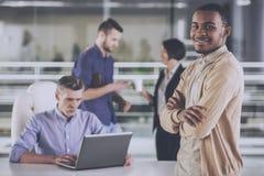Młoda afrykańska biznesmen pozycja z krzyżującymi ręk ludźmi biznesu na tle zdjęcie stock