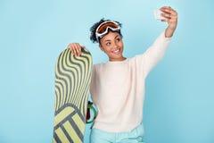 Młoda afrykańska kobieta na błękit ściany zimy sporta jazda na snowboardzie pojęcia selfie pracownianych fotografiach Zdjęcie Royalty Free
