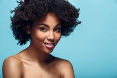 Młoda afrykańska kobieta odizolowywająca na błękit ściany mody photoshoot pracowniany ono uśmiecha się fotografia stock