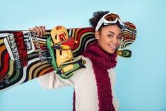 Młoda afrykańska kobieta odizolowywająca na błękit ściany zimy sporta jazda na snowboardzie pojęcia bocznego widoku pracownianym  Zdjęcia Royalty Free