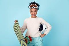 Młoda afrykańska kobieta odizolowywająca na błękit ściany zimy sporta jazda na snowboardzie pracownianego pojęcia horyzontalnym o Obraz Stock