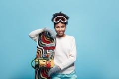 Młoda afrykańska kobieta odizolowywająca na błękit ściany zimy sporta jazda na snowboardzie pracownianego pojęcia horyzontalnym s Obrazy Stock
