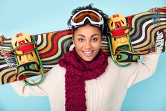 Młoda afrykańska kobieta odizolowywająca na błękit ściany zimy sporta jazda na snowboardzie pracownianego pojęcia rozochoconym za Obraz Stock