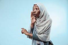Młoda afrykańska kobieta szepcze sekret za ona oddaje błękitnego tło zdjęcia stock