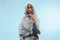 Młoda afrykańska kobieta szepcze sekret za ona oddaje błękitnego tło obrazy royalty free