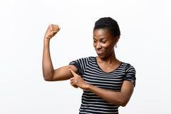 Młoda Afrykańska kobieta wskazuje jej ręka mięśnie obraz royalty free