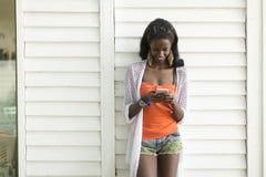 Młoda afrykańska kobieta z telefonem komórkowym Fotografia Stock