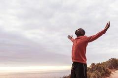 Młoda Afrykańska mężczyzna pozycja na śladzie na zewnątrz obejmowanie natury Fotografia Stock