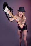 Młoda agresywna kobieta z tatuaż niszczącą gitarą Fotografia Stock