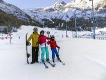 Młoda aktywna rodzina cieszy się zima sporty w powabnym Szwajcarskim kurorcie opłata Zdjęcie Stock