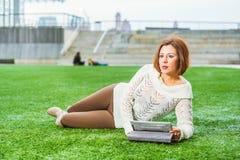 Młoda Amerykańska kobieta relaksuje na zielonym gazonie Zdjęcie Royalty Free