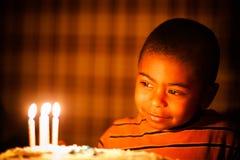 Młoda amerykanin afrykańskiego pochodzenia chłopiec patrzeje urodzinowe świeczki zdjęcie stock