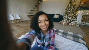Młoda amerykanin afrykańskiego pochodzenia dziewczyna gawędzi online rozmowę używać smartphone kamerę na bożych narodzeniach w do zdjęcie wideo