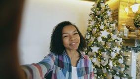 Młoda amerykanin afrykańskiego pochodzenia dziewczyna gawędzi online rozmowę używać smartphone kamerę w domu blisko choinki zdjęcie wideo